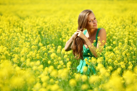 woman on oilseed field close portrait photo