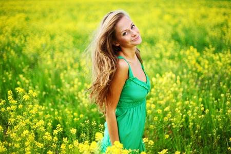 woman on oilseed field close portrait photo