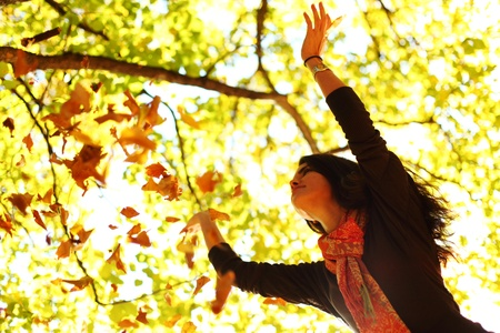 woman drop up leaves in autumn park Stock Photo - 10522871