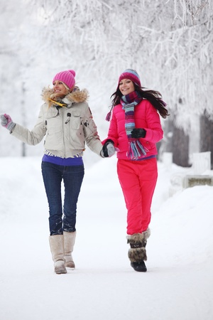 throw up: two winter women run by snow frosted alley