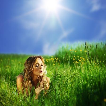 girl blow on dandelion on green field Stock Photo
