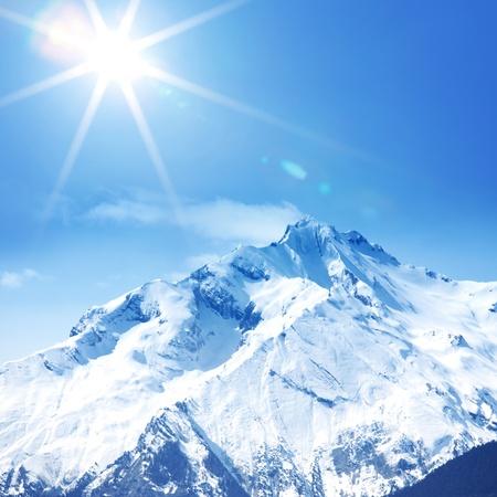 montañas nevadas: parte superior del Sol de las montañas en cielo azul