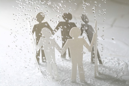 paper team linked together under rain weather concept Stock Photo - 10535346