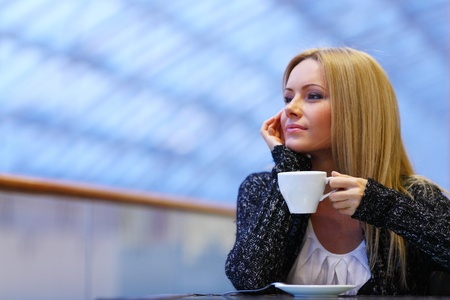 young woman drink coffee on modern background photo