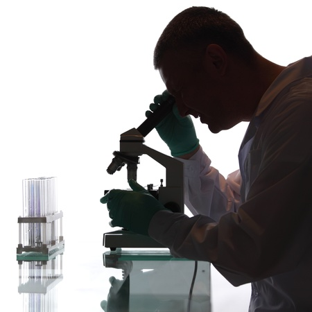 medical scientist: Scientist looking into a microscope in a laboratory Stock Photo