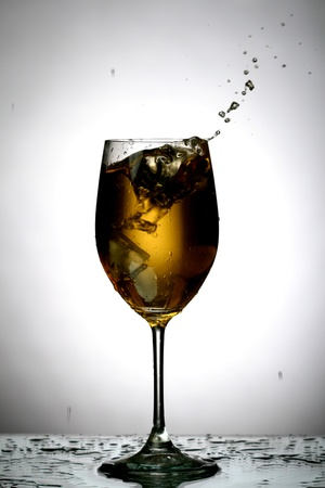 bartend: alcohol splash on gray background Stock Photo