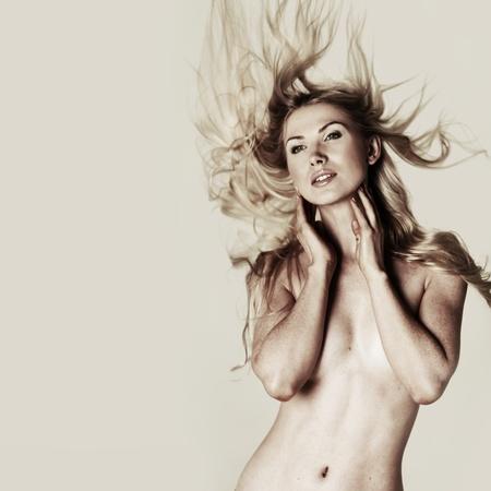 young nude girl: nackte Frau schüttelt den Haaren auf einem beige Hintergrund Lizenzfreie Bilder