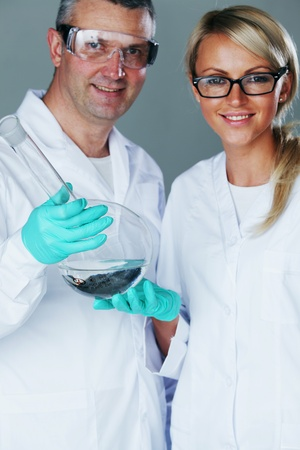 Chemistry researchers holding a secret green chemical substance photo