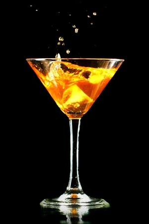 splash mixed: alcohol splash in martini glass on black background Stock Photo