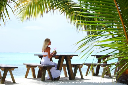 woman sitting in a tropical cafe on the background of a  palm trees and sky and sea Stock Photo