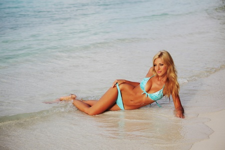salud sexual: mujer tendido en la arena de la costa del Oc�ano Foto de archivo