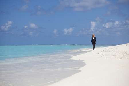 business woman with briefcase walking on the desolate ocean coast Stock Photo - 10895852