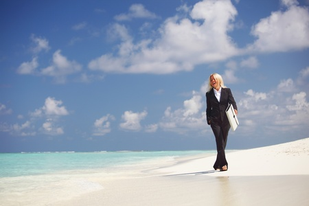 business woman with briefcase walking on the desolate ocean coast photo