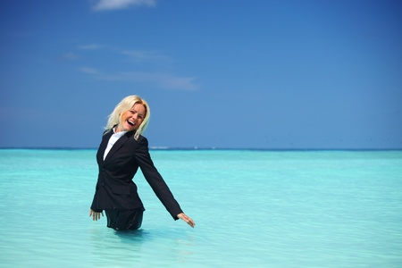 business woman stay in ocean waves photo