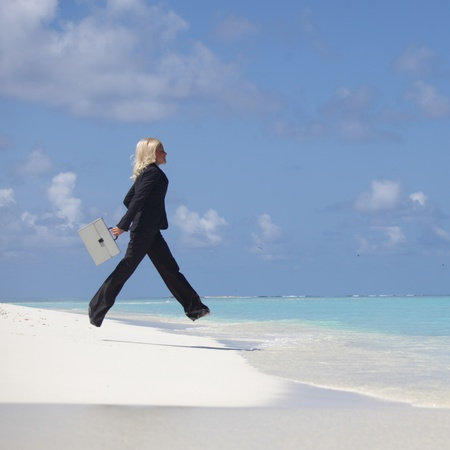 business woman jump in ocean waves photo