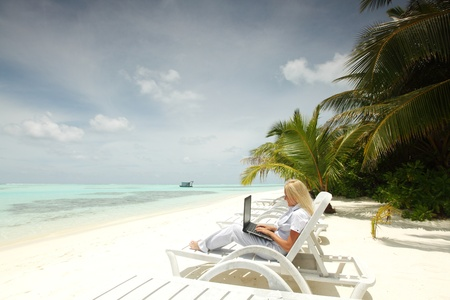 business lounge: business woman with laptop lying on a chaise lounge in the tropical ocean coast