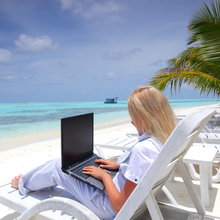 business woman with laptop lying on a chaise lounge in the tropical ocean coast Stock Photo - 10896032