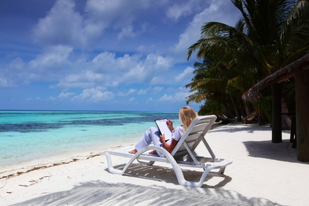 business woman with blank paper lying on a chaise lounge in the tropical ocean coast Stock Photo - 10895932