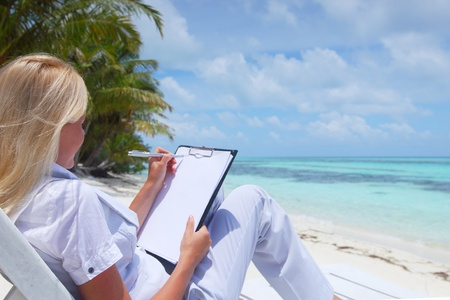 business woman with blank paper lying on a chaise lounge in the tropical ocean coast Stock Photo - 10895844