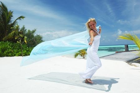 scarf beach: mujer con una tela blanca en sus manos en la playa