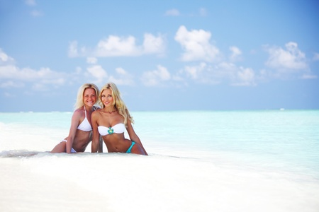 Two girls sitting on the ocean coast Stock Photo - 10895881