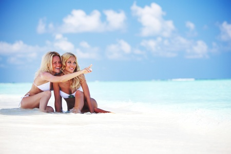 Two girls sitting on the ocean coast Stock Photo - 10895849