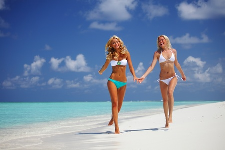 tanned body: Two girls run along the ocean coast