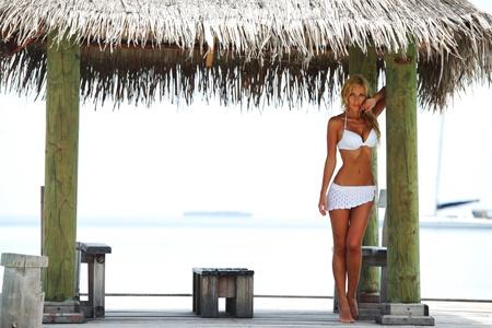 Frau auf der Veranda des tropischen Hauses Standard-Bild