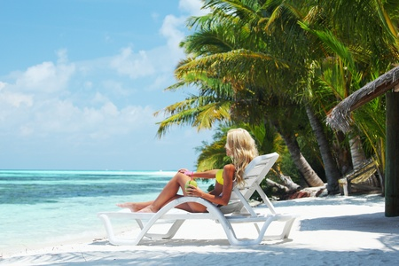 tropical woman on lounge with a coconut cocktail Stock Photo - 10895960