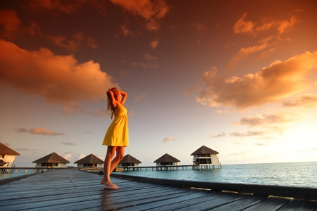 woman in a dress on a bridge home sea and the maldivian sunset on the background Stock Photo - 10896015