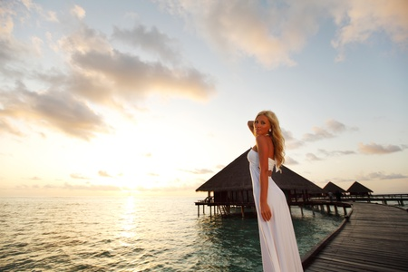 woman in a dress on a bridge home sea and the maldivian sunset on the background Stock Photo - 10895903