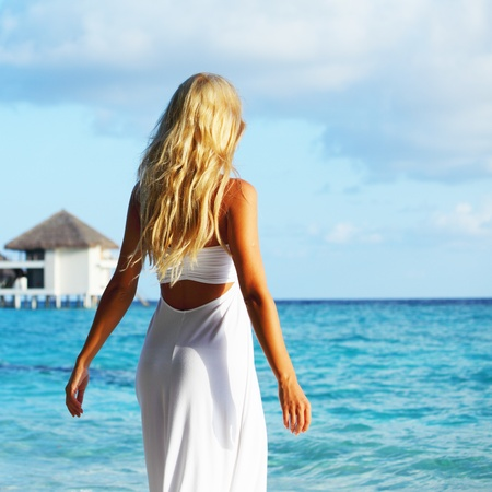 woman on tropical beach house back on the background Stock Photo - 10895851