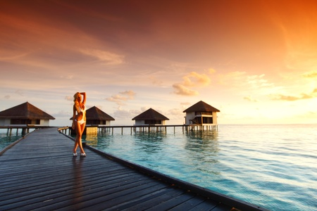 woman in a dress on a bridge home sea and the maldivian sunset on the background Stock Photo - 10896037
