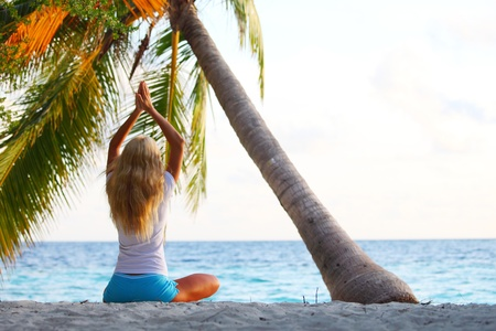 yoga woman on sea coast under palm