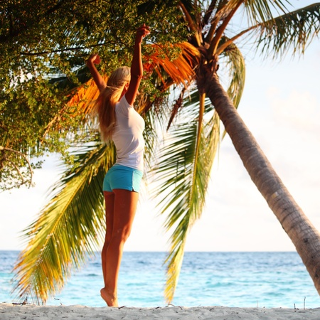 yoga woman on sea coast under palm photo