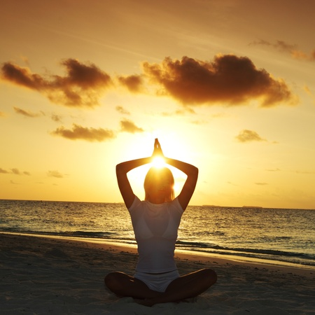 active holiday: sunset yoga woman on sea coast Stock Photo