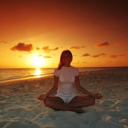 woman meditation: sunset yoga woman on sea coast Stock Photo