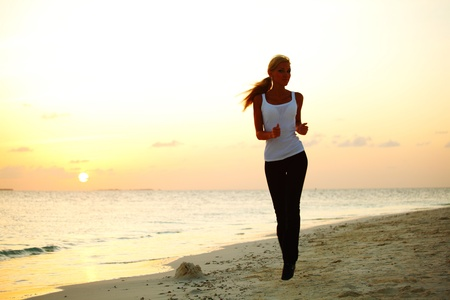 woman run along the sea coast of sunrise behind Stock Photo - 10895879