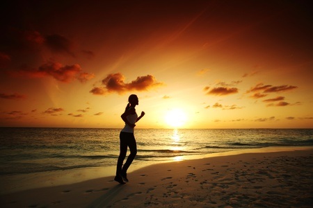 woman run along the sea coast of sunrise behind Stock Photo - 10896021