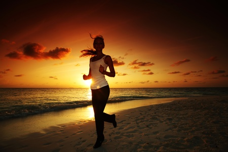 woman run along the sea coast of sunrise behind photo