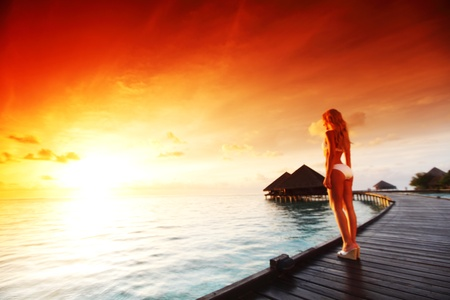 fresh morning: woman in a dress on a bridge home sea and the maldivian sunset on the background