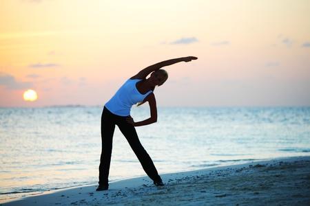 mulher do sol yoga na costa de mar Imagens