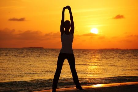 Sonnenuntergang Yoga Frau auf Küste