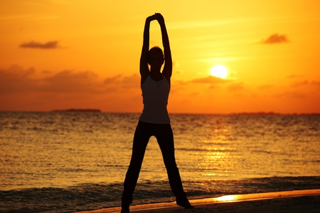 sunset yoga woman on sea coast Stock Photo - 10895894