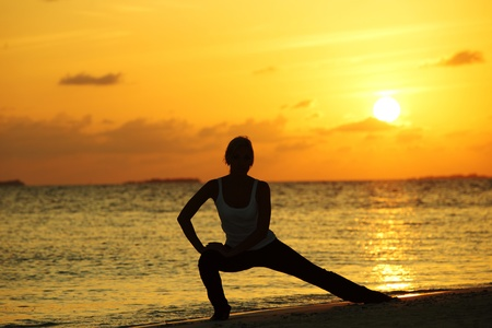 sunset yoga woman on sea coast Stock Photo - 10895834