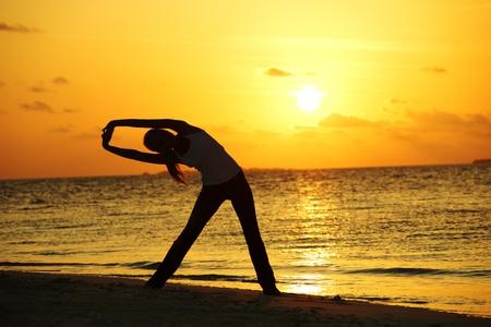 sunset yoga woman on sea coast Stock Photo