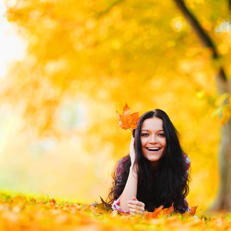 only young adults: woman on leafs in autumn park Stock Photo