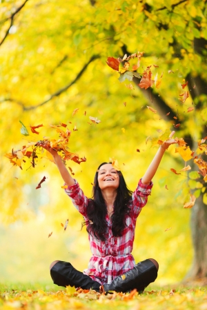 woman in autumn park drop up leaves Stock Photo - 10913690