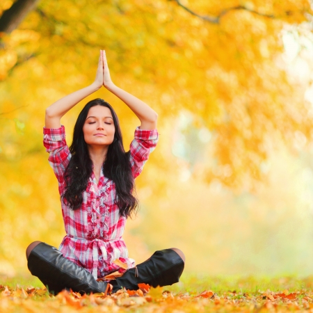 yoga autumn woman on leafs in park photo
