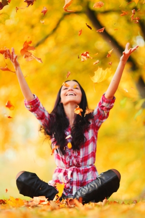 fall fun: woman in autumn park drop up leaves Stock Photo